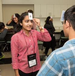 Students play a card game where they hold cards to their forehead.